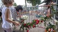 Zeichen der Trauer: Anwohner legen Blumen am Ort der Brandkatastrophe ab.