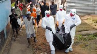 In Liberias Hauptstadt Monrovia tragen Helfer die Leiche eines jungen Mannes weg, der am Ebola-Virus gestorben sein soll.