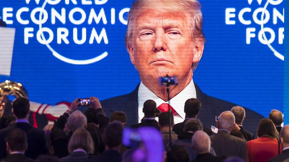 Im vergangenen Jahr war er noch dabei: Teilnehmer verfolgen die Übertragung der Rede des amerikanischen Präsidenten Donald Trump auf einem großen Bildschirm beim 48. Weltwirtschaftsforums im Jahr 2018