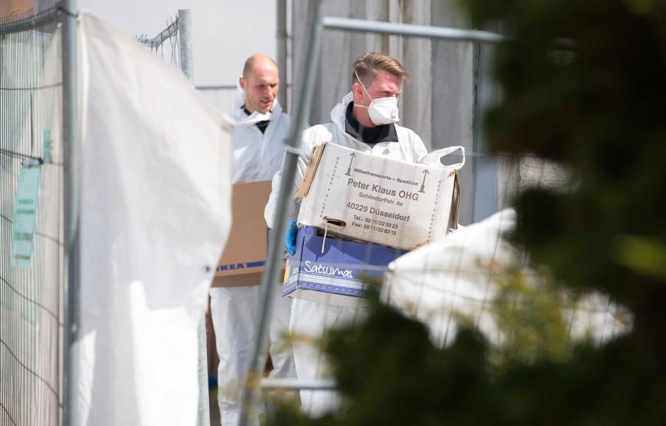 Polizeibeamte tragen Kartons aus dem Haus des beschuldigten Ehepaares.