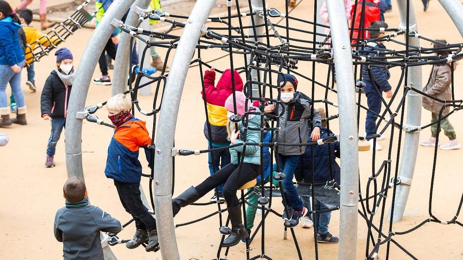 Kinder spielen während der Pause in einem Klettergerüst auf dem Schulhof der Holzhausenschule in Frankfurt. Wegen der Corona-Pandemie tragen sie Mund-Nase-Schutz.