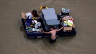 """Bewohner retten, was noch zu retten ist in den Fluten nach dem Tropensturm """"Harvey""""."""