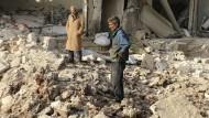 Verlierer auf allen Seiten: Zwei Männer durchsuchen nach einem Luftangriff in Aleppo die Trümmer.