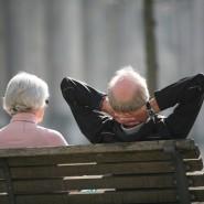 Ein Rentnerpaar auf einer Bank vor dem Reichstag in Berlin.