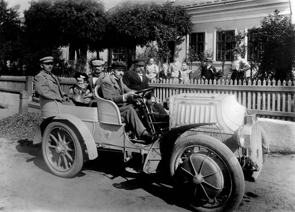 Ferdinand Porsche am Steuer eines Lohner-Porsche Mixte vor seinem Geburtshaus, im Jahr 1902. Auf dem Beifahrersitz sein Vater, auf den Rücksitzen seine Brüder und die nächste Generation.