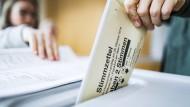 Eine Wählerin wirft am Morgen ihren Stimmzettel für die Landtagswahl in Hessen in die Wahlurne.