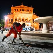 Ein Mitarbeiter der Frankfurter Stadtreinigung entfernt mit einer Schaufel Abfall vor der Alten Oper, nachdem Besucher den Platz verlassen mussten.