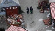 Polizisten stehen in den Trümmern auf dem Weihnachtsmarkt an der Gedächtniskirche.
