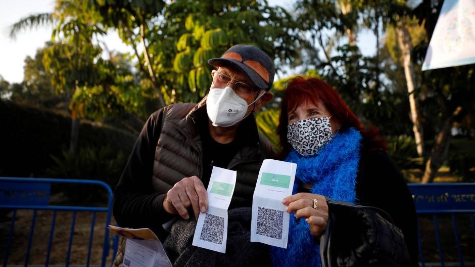 """Ein Paar aus einer Seniorenresidenz in Tel Aviv mit seinen """"Grünen Pässen"""" am 24. Februar"""