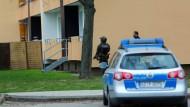 Ein Einsatzfahrzeug der Polizei steht vor einem Mehrfamilienhaus in Salzgitter, das von der Polizei gestürmt wurde.