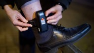 Ein Mann bekommt eine elektronische Fußfessel angelegt (Bild: 17.12.2012)