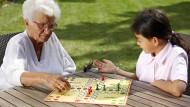Jung trifft Alt in einer Seniorentagesstätte in Frankfurt am Main beim Mensch-Ärger-Dich-Nicht-Spiel