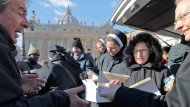 Katholische Nonnen verteilen auf dem Petersplatz Lebensmittel und Getränke an Bedürftige.
