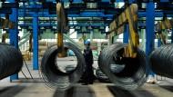 Ein Arbeiter steht neben Stahlkabeln in einer Stahlfabrik in der ostchinesischen Provinz Shandong.