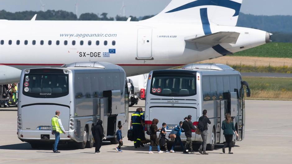 Flüchtlinge aus griechischen Flüchtlingslagern steigen aus dem Flugzeug am Flughafen Kassel-Calden und gehen zu einem Bus.