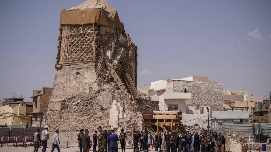 Personen stehen auf dem Gelände der Al-Nuri-Moschee, in der 2014 das Kalifat des Islamischen Staates ausgerufen wurde.