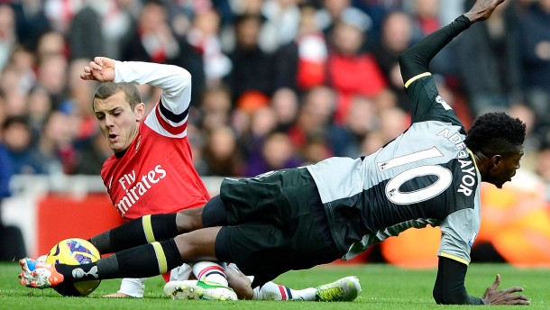 Arsenal's Jack Wilshere challenges Tottenham Hotspur's Emmanuel Adebayor during their English Premier League soccer match in London