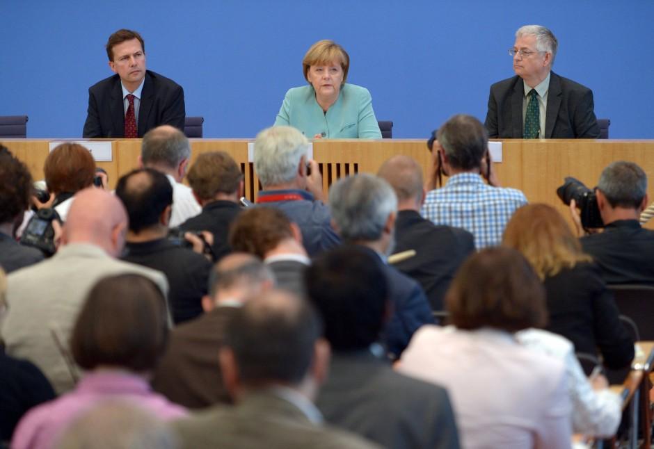 Vollbesetzte Bundespressekonferenz:  Auf dem Podium sitzen neben Merkel Regierungssprecher Steffen Seibert (l.) und der Vorsitzende der Bundespressekonferenz Gregor Mayntz (r.)