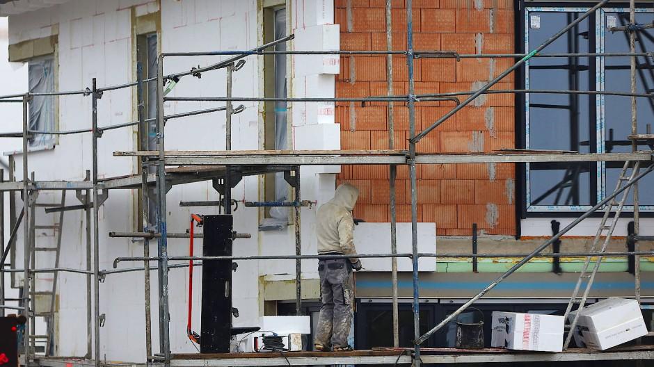 Ein Handwerker bringt auf einem Baugrundstück Dämmmaterial an einen Neubau an.