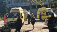 Krankenwagen, Rettungskräfte und Polizisten sind nach einer Explosion in der Mensa der Berufsschule auf der Halbinsel Krim vor dem Gebäude zu sehen.