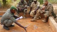 Ein malischer Soldat (links), Teilnehmer der europäischen Trainingsmission EUTM Mali, bespricht während einer Übung mit einem deutschen Ausbilder im Geländesandkasten eine Manöverstrategie.