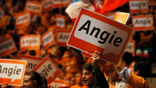 "Supporters hold up placards that read ""Angie"", the nickname of German Chancellor and conservative CDU leader Merkel, at the CDU's election campaign rally in Duesseldorf"