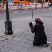 Eine bettelnde Frau kniet auf dem Gehweg einer Einkaufsstraße.