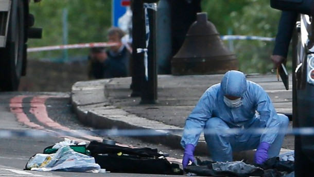 A police forensics officer investigates a crime scene where one man was killed in Woolwich