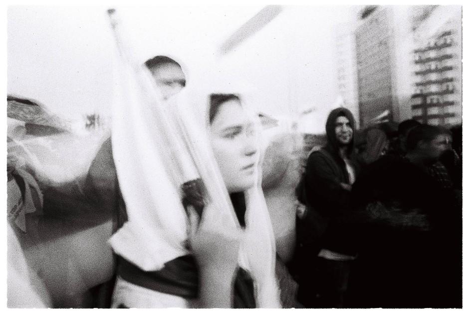 Die Fahne als Brautschleier: eine junge Demonstrantin schützt sich vor dem einsetzenden Regen.