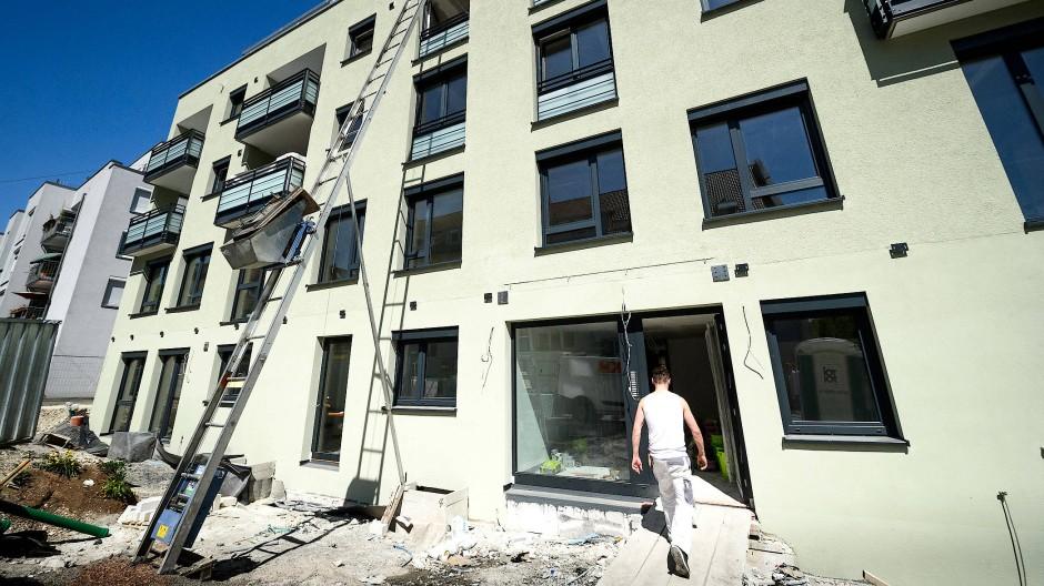 Ein Arbeiter geht über die Baustelle eines zukünftigen Wohnhauses.