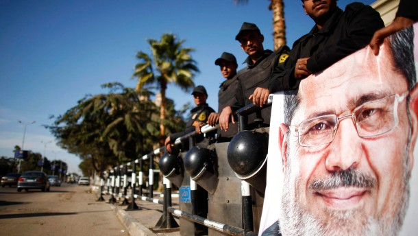 Policemen stand guard near a poster outside the constitutional court put up by supporters of Egyptian President Mohamed Mursi as they stage a sit-in, in Cairo