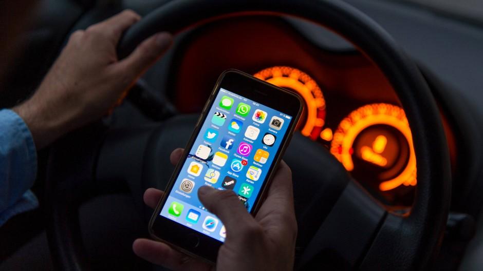 Das Halten des Handys setzt nach Ansicht der Autofahrerin den Einsatz der Hände voraus. Die Richter in Köln sahen das anders.