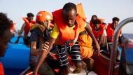Ein Geflüchteter verlässt vor der Küste Libyens ein Schlauchboot: Die Crew der Rettungsorganisation Sea Eye hat ihn und die anderen Geflüchteten an Bord genommen.