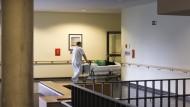 Ein Krankenpfleger schiebt eine Patientin im Krankenbett durch das Helios Klinikum Berlin-Buch.
