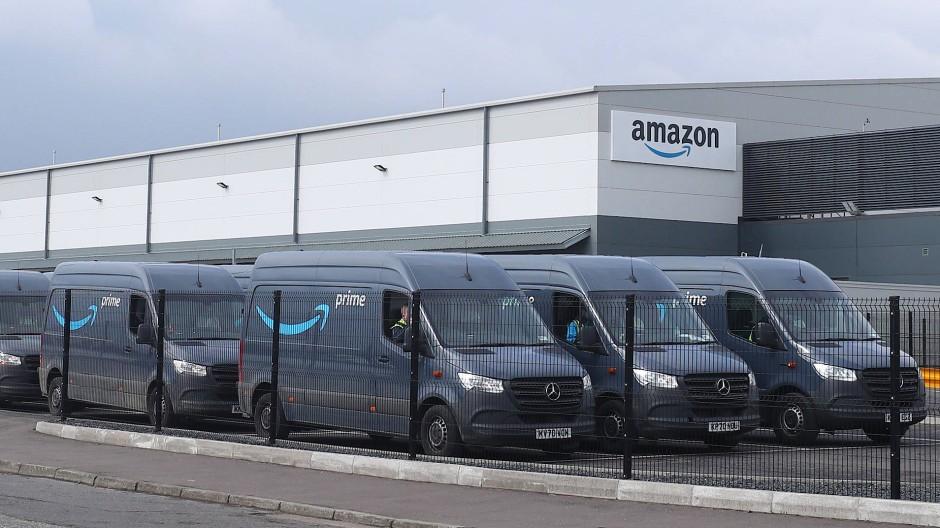Elektro-Lieferwagen von Amazon stehen auf einem Parkplatz vor einem Warenlager des Onlineversandhändlers in Belfast.
