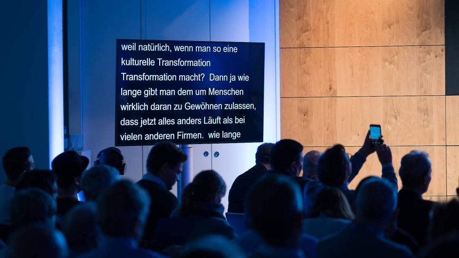 Lesen statt lauschen: Vorn steht der Sprecher, an der Seite läuft automatisch der gesprochene Text, dank der Software Eve.