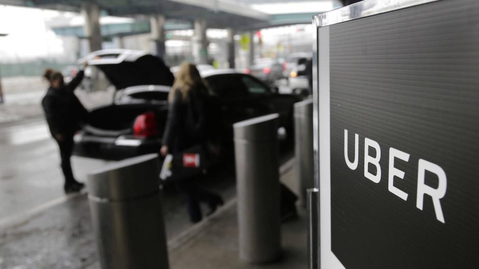 Ein Schild mit dem Logo des amerikanischen Dienstleistungsunternehmens Uber am Abholpunkt von Uber auf dem LaGuardia-Flughafen in New York.