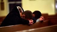 Zwei Männer beten in einer Kirche in der Nähe der Sandy Hook Grundschule in Newtown, in der ein junger Mann 20 Schüler und sechs Erwachsene tötete