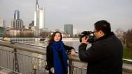 Erklärt den Chinesen Deutschland: Fernsehfrau Linzi setzt sich auf dem Holbeinsteg in Szene.