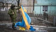 Ein prorussischer Rebell begutachtet in der Nähe von Donezk eine ukrainische Flagge. (Archivbild)