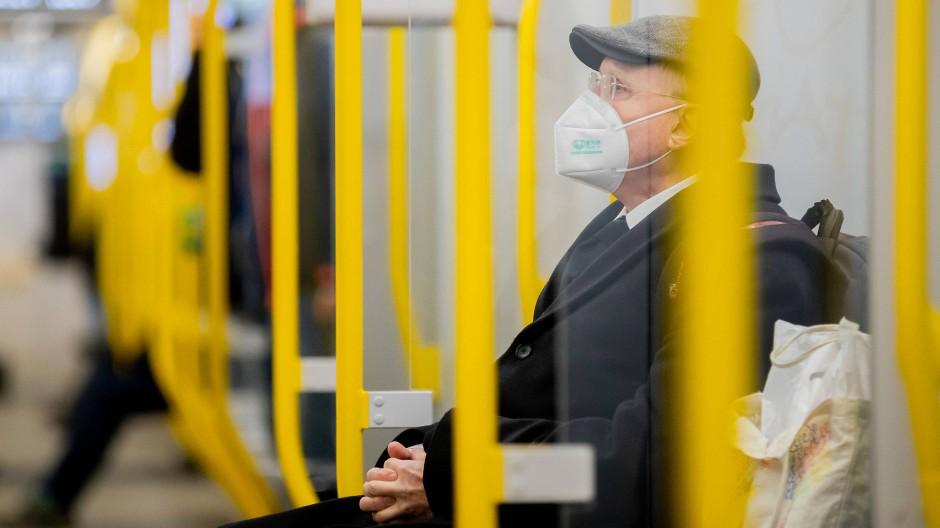 Ein Mann sitzt mit einer FFP2-Maske allein in der U-Bahn in Berlin.