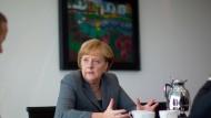"""Angela Merkel in ihrem Büro im Kanzleramt im November 2011. Im Hintergrund das Bild """"Blumengarten in Alsen"""" von Emil Nolde"""