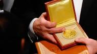 Wirtschaftsnobelpreisträger Dale Mortensen (2010) zeigt seine Medaille.
