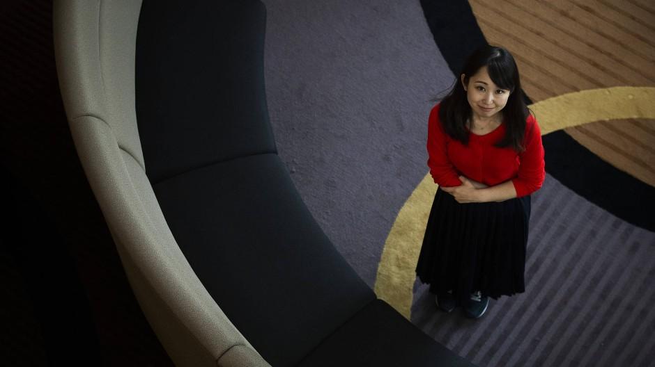 In Sneakers unterwegs statt Highheels: Schauspielerin Yumi Ishikawa wehrt sich auch gegen das Brillenverbot für Frauen am Arbeitsplatz.