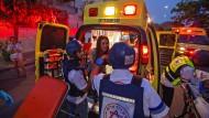 Rettungskräfte in der südisraelischen Stadt Sderot versorgen eine Frau nach einem Raketenangriff aus dem Gazastreifen am 12. Mai