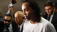 Der ehemalige Fußballstar Ronaldinho wird von der Polizei ins Gerichtsgebäude in Asuncion eskortiert.