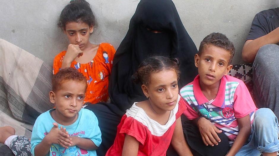 Die Hinterbliebenen eines am Coronavirus Verstorbenen sitzen in der jemenitischen Stadt Aden auf dem Boden.