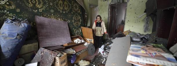 Eine Frau in ihrer durch Mörserbeschuss zerstörten Wohnung in Doneszk