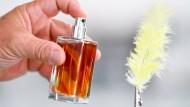 Wie das duftet: Ein Parfümeur besprüht in einem Verkaufsraum eine gelb gefärbte Hühnerfeder.