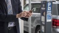 Ein Mann bezahlt in der Schweiz sein Parkticket via Smartphone.